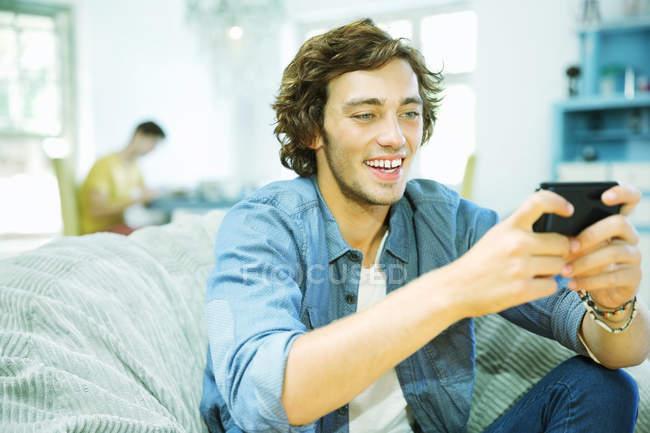 Homem usando o celular no pufe — Fotografia de Stock