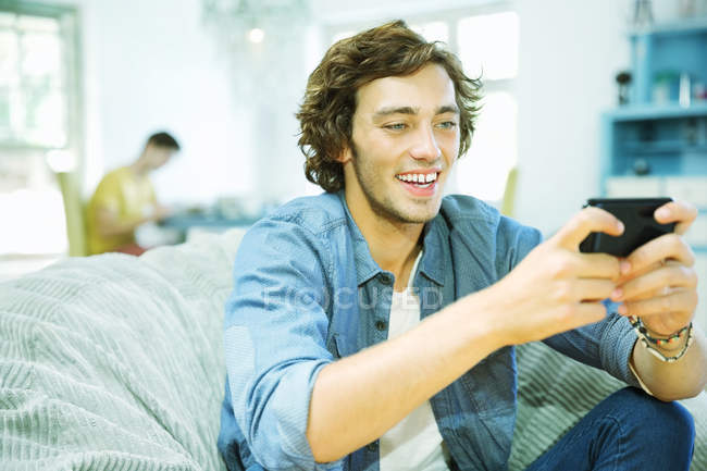 Man using cell phone in beanbag chair — Stock Photo