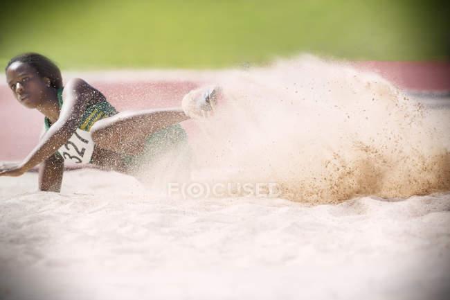 Long jumper pouso na areia — Fotografia de Stock