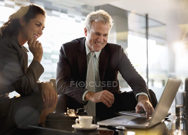 Smiling businessman and businesswoman using laptop in lobby at modern office — Stock Photo
