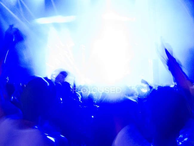 Silhouette of crowd facing illuminated stage — Stock Photo