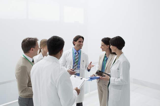 Улыбающиеся врачи обсуждают медицинские карты — стоковое фото