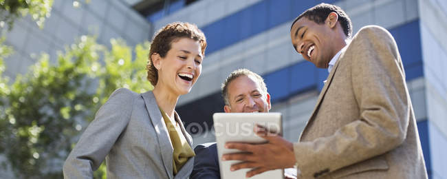 Business people using tablet computer outdoors — Stock Photo