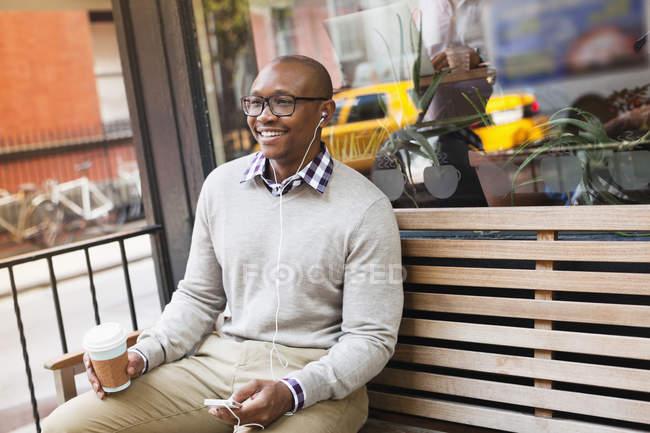 Человек, слушающий наушники на городской улице — стоковое фото