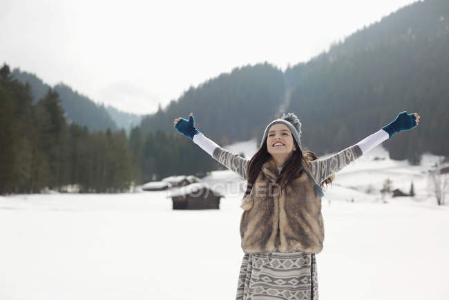 Carefree woman with arms outstretched in snowy field — Stock Photo
