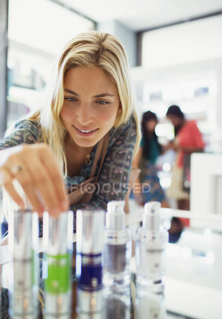 Woman examining skincare products in drugstore — Stock Photo