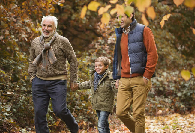 Três gerações de homens caminhando no parque — Fotografia de Stock