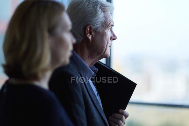 Uomo d'affari e donna d'affari pensieroso guardando attraverso la finestra — Foto stock