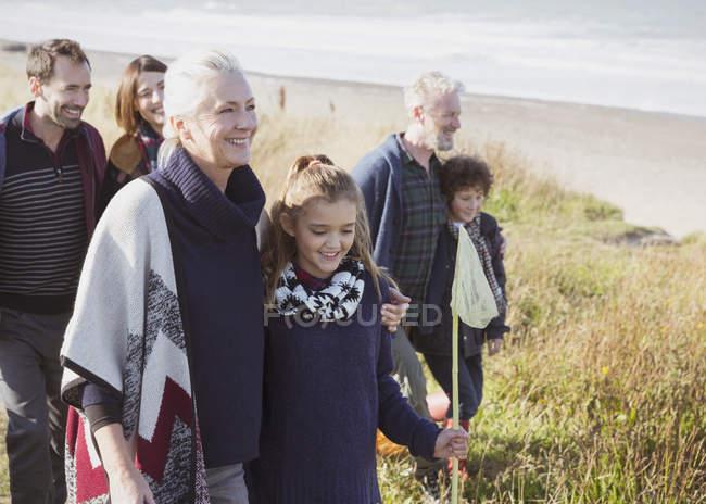 Smiling multi-generation family walking in beach grass — Stock Photo
