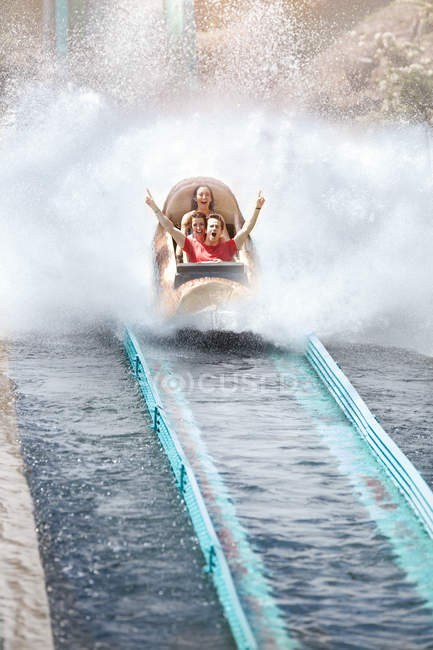 Enthusiastic friends cheering and riding water log amusement park ride — Stock Photo