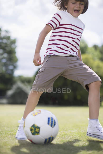 Happy boy playing soccer outdoors — Stock Photo