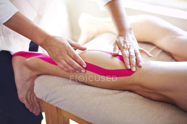 Фізіотерапевт застосування кінезіології стрічки до людини? s ногу — стокове фото