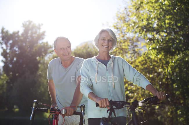 Senior couple walking bicycles in park — Stock Photo