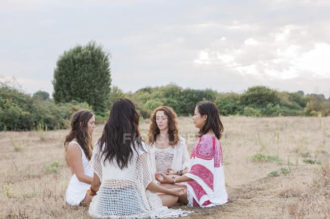 Boho women meditating in circle in rural field — Stock Photo
