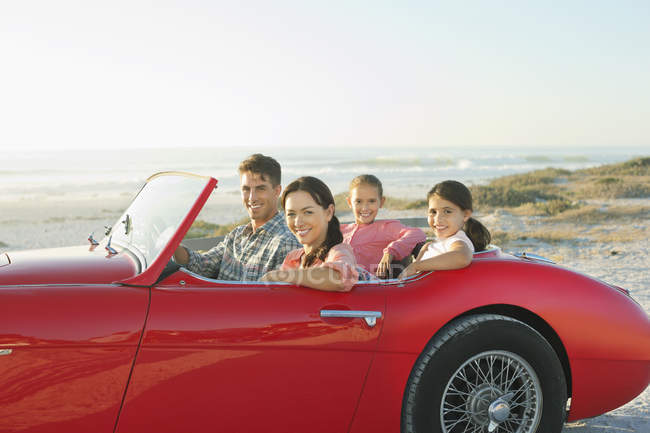 Family in convertible at beach — Stock Photo
