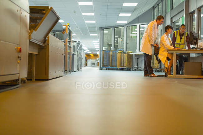Рабочие на компьютере на заводе — стоковое фото