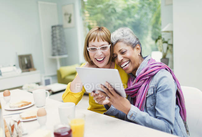 Laughing mature women sharing digital tablet at breakfast table — Stock Photo