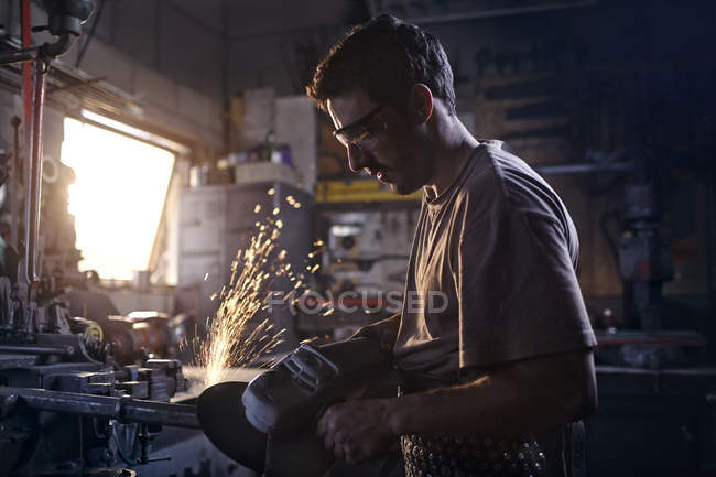Blacksmith using sander in forge — Stock Photo