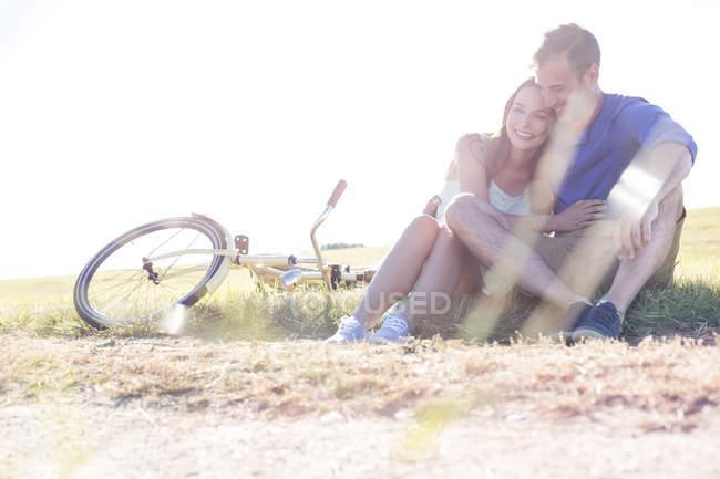 Liebevolles junges Paar umarmt sich in der Nähe von Fahrrad im ländlichen Gras — Stockfoto