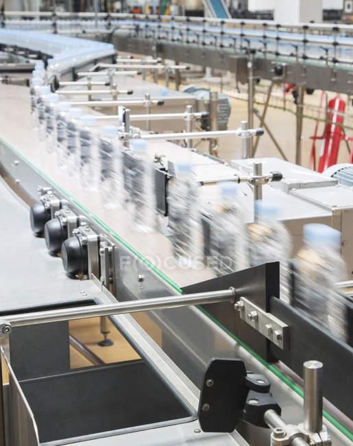 Бутылки на конвейере на заводе — стоковое фото