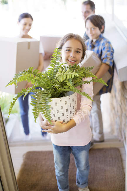 Portrait of smiling family moving belongings into house — Photo de stock