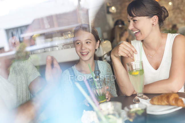 Family laughing at cafe table — Stockfoto