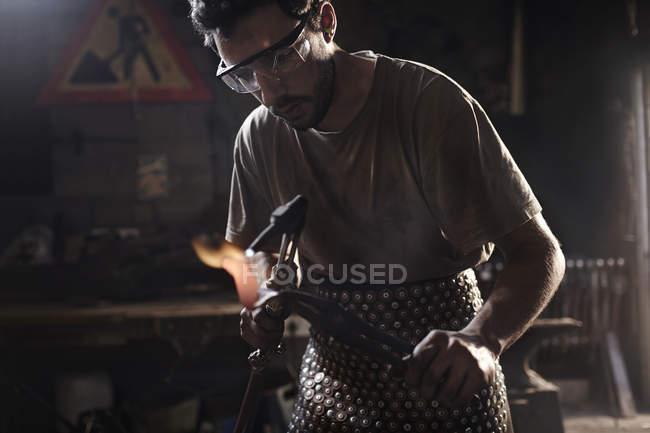 Forgeron utilisant chalumeau dans la forge — Photo de stock