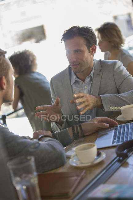 Businessmen talking and gesturing at cafe — Stock Photo