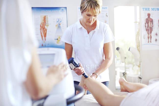 Physical therapist using ultrasound probe on woman?s leg — Stock Photo