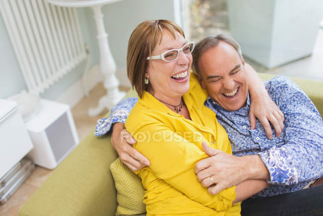 Mature couple laughing and hugging on sofa — Stockfoto