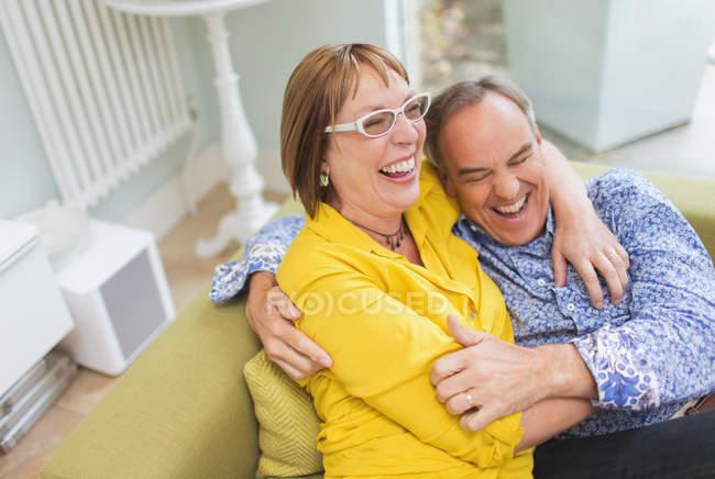 Pareja riendo y abrazando en sofá - foto de stock