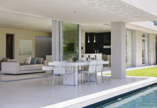 Set mesa no pátio por piscina de casa moderna — Fotografia de Stock