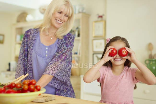 Портрет игривой внучки, закрывающей глаза помидорами на кухне — стоковое фото