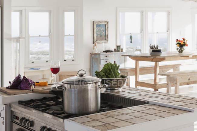 Legumes e copo de vinho na cozinha — Fotografia de Stock