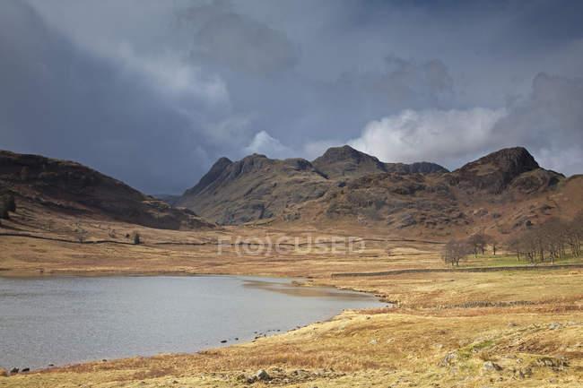 Скалистые холмы озера в дневное время — стоковое фото