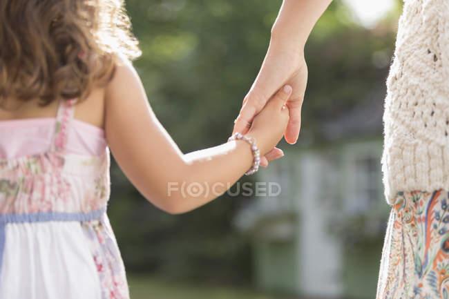 Close up vista posteriore madre e figlia che si tiene per mano — Foto stock