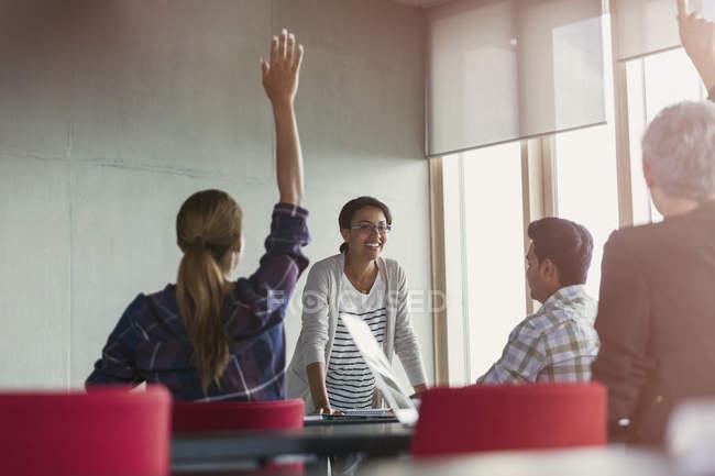 Enseignant et élèves avec les mains levées en classe d'éducation des adultes — Photo de stock