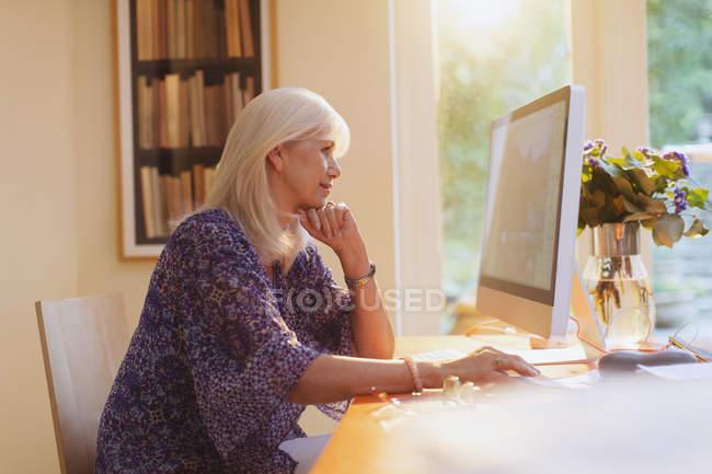 Seniorin arbeitet im Homeoffice am Computer — Stockfoto