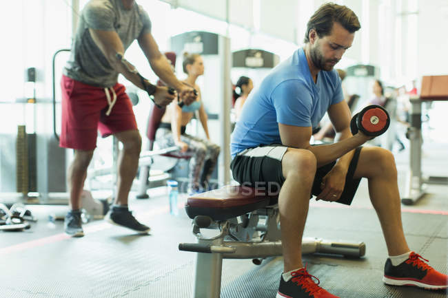 Man doing dumbbell biceps curls at gym — Stock Photo