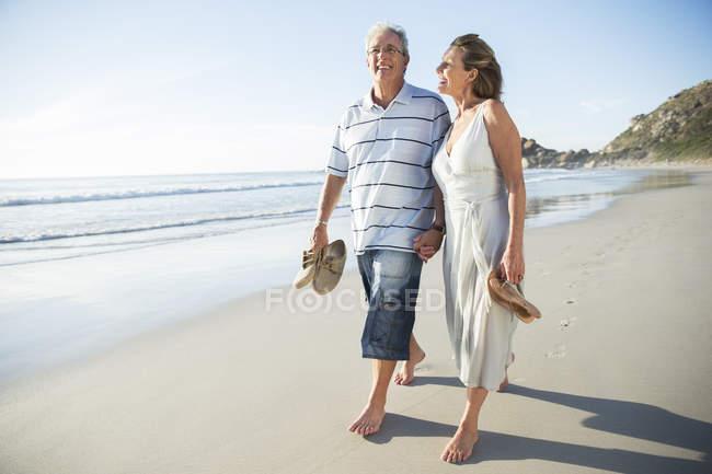 Anziani coppia a piedi sulla spiaggia — Foto stock