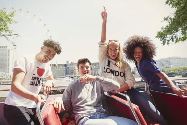 Portrait enthusiastic friends riding double-decker bus, London, United Kingdom — Stock Photo