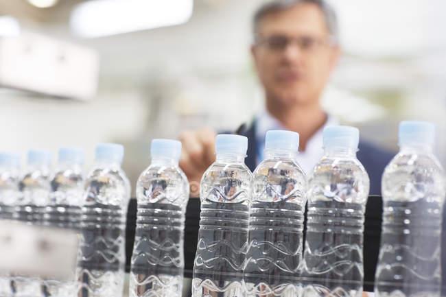 Руководитель, осматривающий бутылки на заводе — стоковое фото