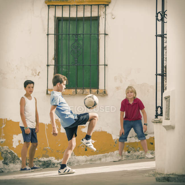 Children playing with soccer ball in alley — Stock Photo
