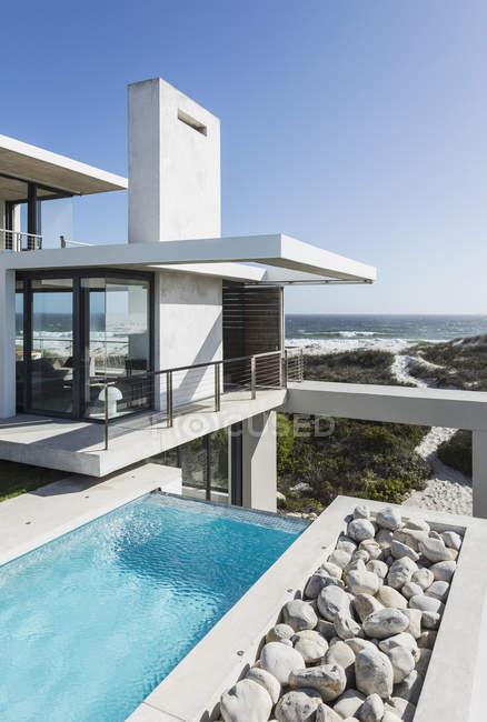 Бассейн и балкон современного дома с видом на океан — стоковое фото