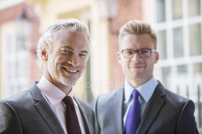 Uomini d'affari sorridenti sulla strada della città — Foto stock