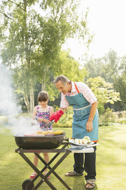 Grandfather and granddaughter grilling at barbecue in backyard — Stock Photo