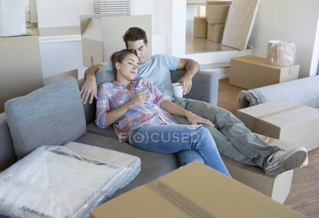 Pareja relajante en el sofá en la casa nueva - foto de stock