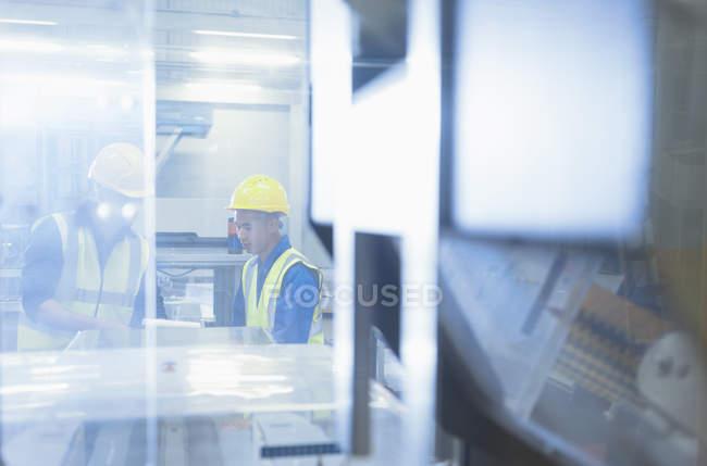 Trabalhadores de falar em máquinas na fábrica — Fotografia de Stock