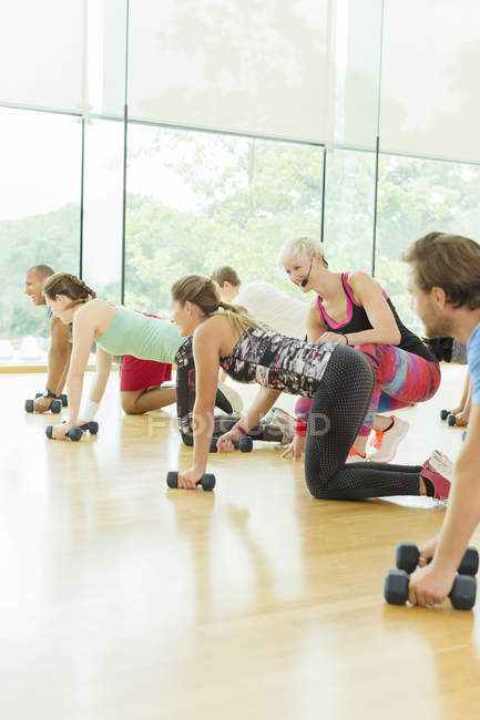 Fitness instructor guiding woman in exercise class — Stockfoto