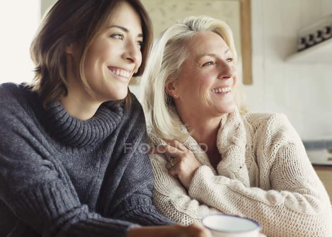 Улыбающиеся мать и дочь в свитерах смотрят в сторону — стоковое фото